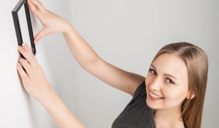 rame decorative femeie care pune o fotografie pe perete