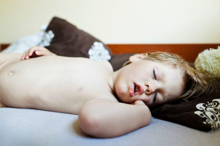 copil care doarme in pat
