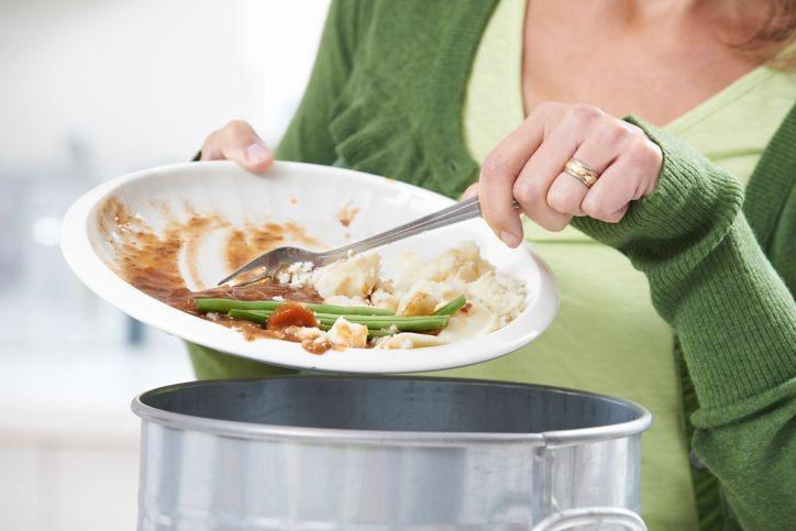femeie mancare gunoi
